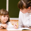 Teacher helps the student with schoolwork in  classroom — Stock Photo