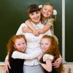 Children hugging their teacher — Stock Photo #31882213