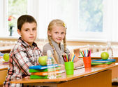 Portrait of schoolkids looking at camera at workplace — Stock Photo
