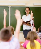 Children raising hands knowing the answer to the question — Stock Photo