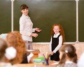 Schoolgirl and teacher near a school board — Stock Photo