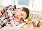 Tired schoolboy in classroom — Stock Photo