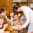 Stock Photo: Teacher helps the schoolkids with schoolwork in classroom