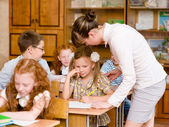 Teacher helps the schoolkids with schoolwork in classroom — Stock Photo