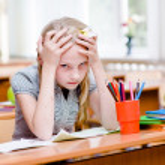 Tired schoolgirl in classroom. — Stock Photo #32852053