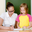 Teacher helps the student with schoolwork in school classroom — Stock Photo