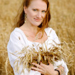 Beautiful girl holding a wheat ears — Stock Photo