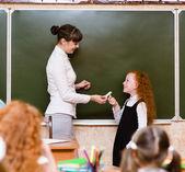 Chica responde a las preguntas de los profesores junto a una junta escolar — Foto de Stock