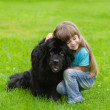 Stock Photo: Girl hugging Newfoundland dog