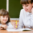 Teacher helping young girl with writing lesson — Stock Photo #34256281