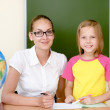 Stock Photo: Teacher helping schoolgirl with schoolwork in classroom