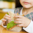 Closeup schoolgirl with sandwich in classroom — Foto Stock