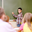 Schoolboy answers questions of teachers near a school board — Stock Photo
