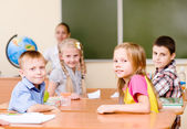 Portrait of schoolkids at workplace with teacher on background — Stock Photo