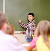 školák odpoví na dotazy učitelů v blízkosti školní rada — Stock fotografie