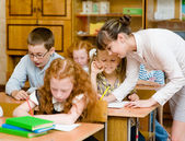 Teacher helps the schoolkids — Stock Photo