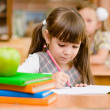 Stock Photo: Girl drawing in copybook in classroom