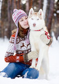 Teen girl embracing cute dog in winter park — Stock Photo