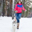 Woman running with dog in winter forest — Stock Photo