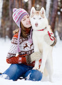 Teen girl embracing cute dog in winter park — Stok fotoğraf