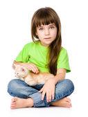 Little girl stroking a kitten. — Stock Photo