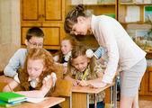 Teacher helps the schoolkids — Stock Photo