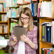 Young focused student using a tablet computer in a library — Stock Photo