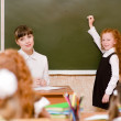Stock Photo: Schoolgirl answers questions of teachers near a school board
