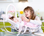Mother feeding newborn daughter with feeding bottle — Stock Photo