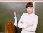 Portrait of teacher standing near blackboard — Stock Photo
