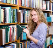 задумчивый студент в библиотеке в окружении книг — Стоковое фото