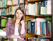 портрет красивой девушки в библиотеке, глядя на камеру — Стоковое фото