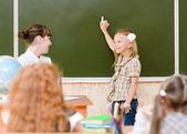 школьница и учитель вблизи школьный совет — Стоковое фото