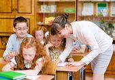 Teacher helps the schoolkids with schoolwork in classroom — Stock Photo