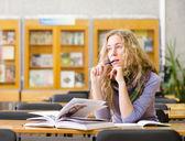 студентка читает книгу в библиотеке. — Стоковое фото