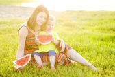 Happy family having picnic on green grass in park — Stock Photo