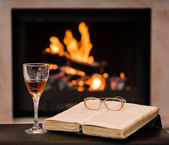 Glass of cognac and book by the fireplace — Stock Photo