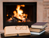 Glasses lie on a book by the fireplace — Zdjęcie stockowe