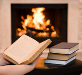 Hands with open book near the fireplace — Stock Photo