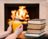 Hands holding cup of coffee near the fireplace — Stock Photo