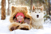 Girl in a fur hat lying next to Husky in the snow in the forest — Stock Photo