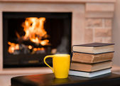 Cup of coffee with books on the background of the fireplace — Stock Photo