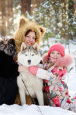 Mother and her daughter hugging Huskies — Stock Photo