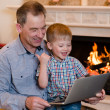 Boy and his grandfather using a notebook. looking at computer — Stock Photo