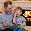 Happy boy and his grandfather using a tablet computer — Stock Photo