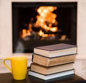 Tazza di caffè con libri sullo sfondo del camino — Foto Stock