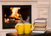 Two cups of coffee with books on the background of the fireplace — Stock Photo