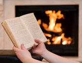 Hands with open book near the fireplace — Foto Stock