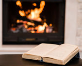 Open book lying near the fireplace — Stockfoto