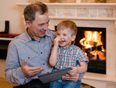 Happy boy and his grandfather using a tablet computer — Stockfoto